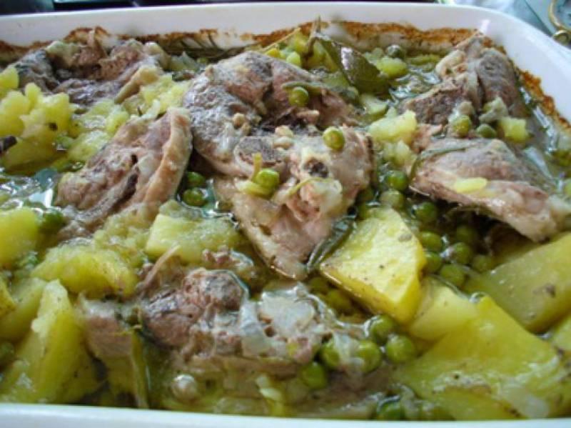 capretto con patate e piselli al forno